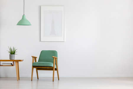 Photo for Retro, mint armchair, wooden table and framed poster in a bright minimalist interior with copy space - Royalty Free Image