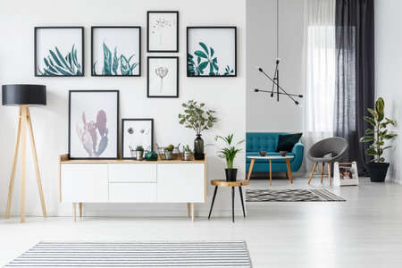 Photo for White living room interior with botanical posters on the wall and sofa in the background - Royalty Free Image