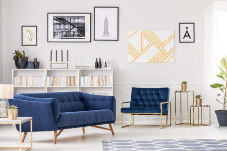 Photo for Art collection, white bookshelf, blue sofa and armchair in modern living room interior - Royalty Free Image