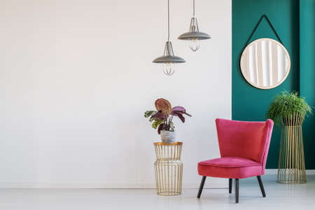 Foto de Plant on golden table next to a pink armchair on a white, empty wall in lobby interior - Imagen libre de derechos