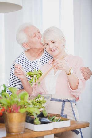 Foto de Senior couple cooking dinner in the kitchen, kissing each other and smiling - Imagen libre de derechos