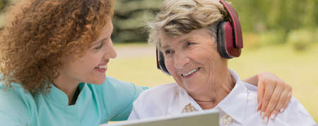 Foto de Close-up of a smiling old lady wearing headphones, with her nurse - Imagen libre de derechos
