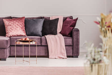 Photo pour Copper table next to a violet sofa with decorative cushions in pink woman's living room interior - image libre de droit