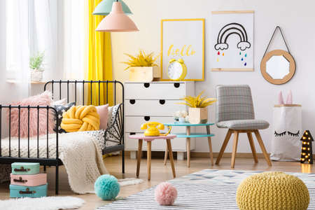 Foto de Yellow pouf and grey chair in colorful kid's bedroom interior with poster on the wall - Imagen libre de derechos