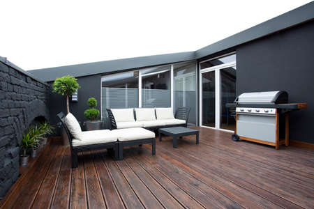 Photo pour Grill and white garden furniture on wooden floor of terrace with plants and black brick wall - image libre de droit