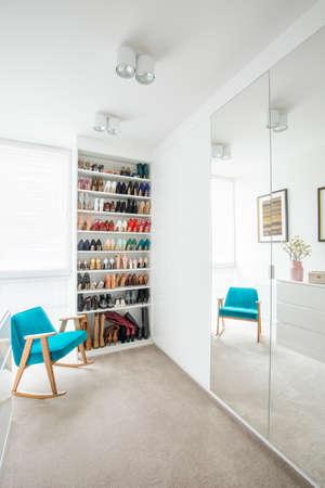 Foto für Bright dressing room interior with tall, built-in shoe shelves and a walk-in wardrobe hidden behind big mirrors - Lizenzfreies Bild