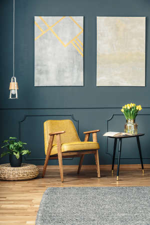 Photo for Yellow armchair between a plant on a wicker ottoman and a side table with tulips and an open book in a dark living room interior with a gray rug - Royalty Free Image