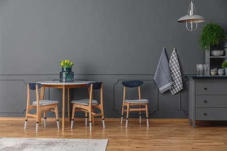 Foto de A table and three chairs next to a rug and grey shelves in simple kitchen interior - Imagen libre de derechos