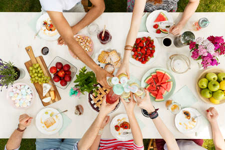 Photo for High angle of multicultural friends toasting at a table with healthy food for vegetarians - Royalty Free Image