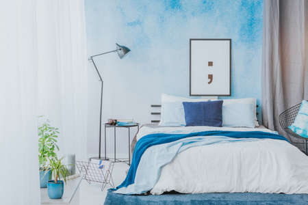 Photo for Romantic bedroom interior with blue accents, poster, lamp and watercolor paint on the wall - Royalty Free Image