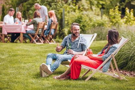 Foto de Friends relaxing on sunbeds and drinking beer in the garden - Imagen libre de derechos