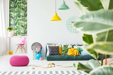 Photo for Toys lying around on the floor in bright kids room interior with plants and green sofa - Royalty Free Image