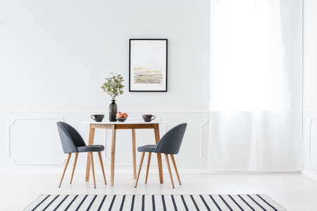 Foto de Small dining furniture set and a striped rug in a minimalist white interior with art above the table - Imagen libre de derechos