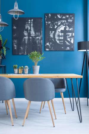 Foto de Plant on wooden table in dining room interior with black paintings on blue wall - Imagen libre de derechos