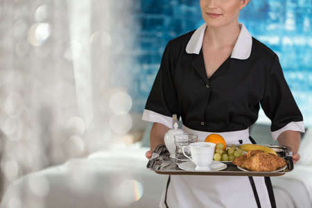 Foto de Maid holding a tray with fruit, coffee, water and croissants for a hotel guest - Imagen libre de derechos