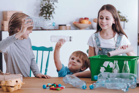 Foto de Siblings having fun while segregating waste at home - Imagen libre de derechos
