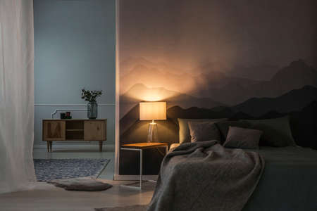 Photo for Bedroom interior at night with warm light of lamp on a bedside table near a wooden cupboard - Royalty Free Image
