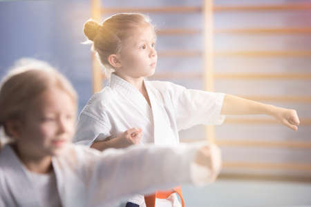 Photo pour Girl in white kimono practicing karate during extra-curricular class at school - image libre de droit