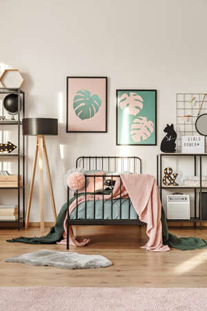 Photo pour Two simple posters with Monstera Deliciosa leaves hanging above metal bed in girl room interior - image libre de droit