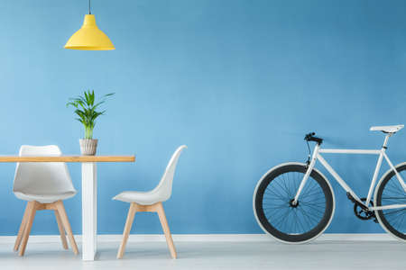 Foto de Minimal, modern interior with two chairs, a bicycle, a table with a plant on it and a yellow lamp above, against blue wall - Imagen libre de derechos