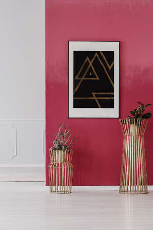 Photo pour Modern poster with triangles hanging on red wall in lobby interior with golden plant pots - image libre de droit