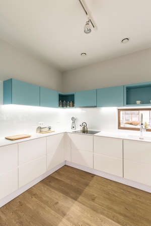 Photo pour Side view of a corner in white and blue kitchen interior with wooden floor - image libre de droit