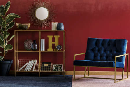 Foto de Golden metal rack with books and decor standing in burgundy room interior with navy blue armchair and potted plant - Imagen libre de derechos