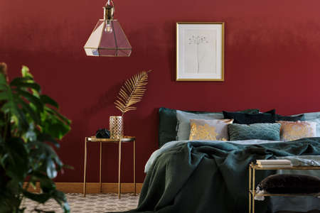 Photo pour Simple poster hanging above bed with many cushions and green blanket standing in bedroom interior with golden furniture - image libre de droit