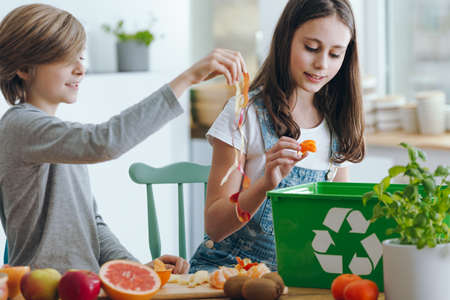 Photo pour Girl and boy trowing out fruits waste into green recycling container - image libre de droit