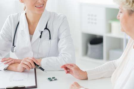Foto de Close-up of a doctor wearing a white coat and stethoscope prescribing medication and supplements to a senior patient - Imagen libre de derechos
