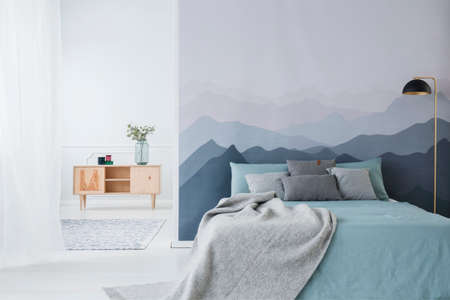 Photo for Blue bed with grey blanket against mountain wallpaper in simple bedroom interior with wooden cupboard - Royalty Free Image