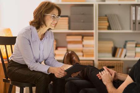 Foto de Elder therapist sitting in a chair and listening to a man in front of her - Imagen libre de derechos
