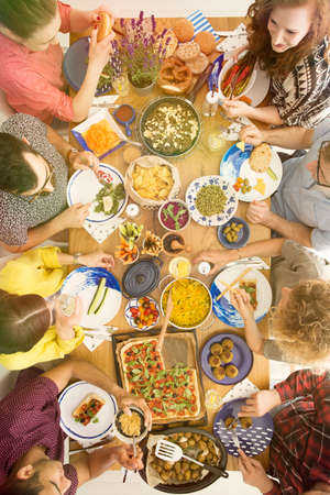 Photo pour High angle of people sitting at a table during an organic, bio, vege meal - image libre de droit