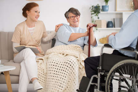 Foto de Beautiful nurse spending time with a disabled senior couple in a nursing home - Imagen libre de derechos