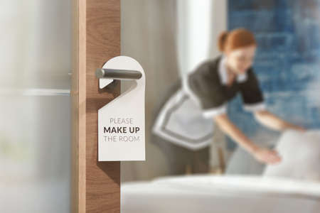 Photo for A housemaid cleaning a room in the background and door with a sign at the front - Royalty Free Image