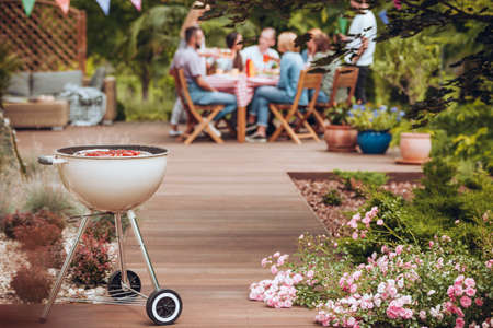 Photo pour Grill with sausages in the garden with flowers and group of friends celebrating in the background - image libre de droit