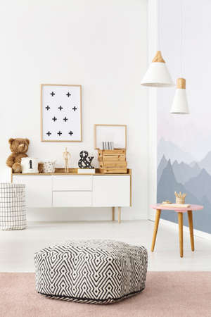 Foto de Black and white pouf with pattern placed in bright kids room interior with posters and decor on wooden cupboard - Imagen libre de derechos