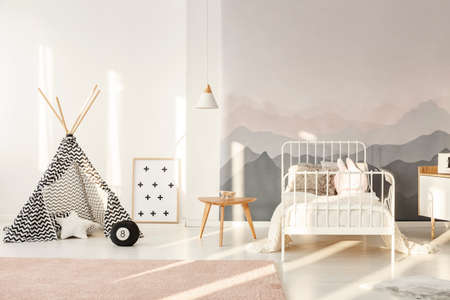 Photo for Patterned teepee standing in bright kids room interior with white bed, mountain wallpaper and powder pink carpet - Royalty Free Image
