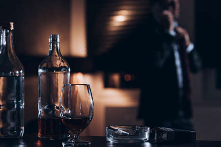 Photo for Bottle, glass with alcohol and cigarettes with a businessman in the background - Royalty Free Image