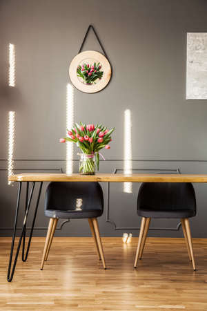 Photo pour Grey chairs at wooden table with flowers in dining room interior with decor on the wall - image libre de droit