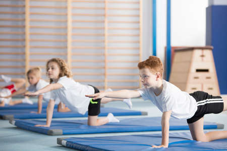 Photo pour Group of children doing gymnastics on blue mats during physical education class at school - image libre de droit