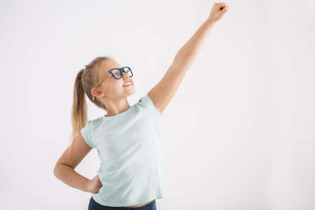 Photo pour Portrait of a young girl with her arm and fist up and the other arm on a hip in a superhero pose on white wall background - image libre de droit