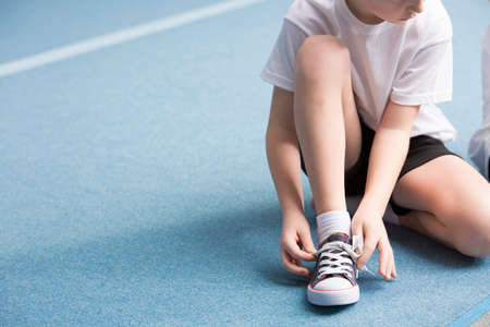 Photo pour Cropped photo of a young boy tying his sports shoes on the court - image libre de droit
