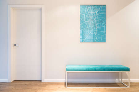 Foto de Turquoise, upholstered bench seat and a city map poster in a white house interior with wooden panels - Imagen libre de derechos