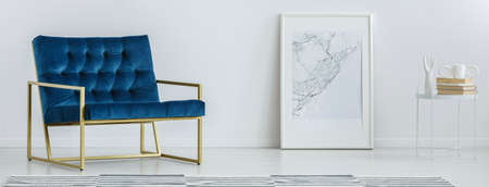 Foto de Royal blue armchair with gold frame standing in white room interior with map poster on the floor and small table with books - Imagen libre de derechos