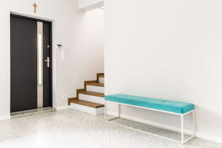 Photo pour Black front door, stairs and a turquoise upholstered bench seat in a white entrance hall interior - image libre de droit