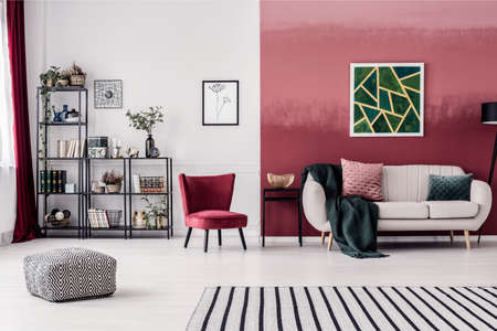 Foto de Striped carpet and pouf in spacious living room interior with red armchair and green painting - Imagen libre de derechos