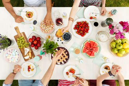 Foto de Mixed-race group of students sitting outside and sharing a meal of fruit, waffles, watermelon and apples on plates - Imagen libre de derechos