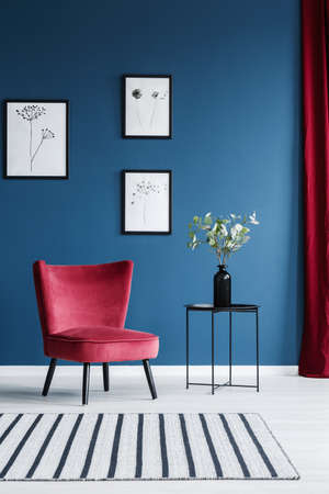 Photo pour Red armchair, patterned rug, flower in a vase and paintings on the blue wall in living room interior - image libre de droit