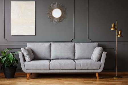Photo for Decorative mirror and modern painting hanging on the wall with molding in dark grey living room interior with fresh plant, gold lamp and bright sofa - Royalty Free Image